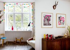 love the dot garland around the window, framed art in natural wood frames and the mid-century piece.
