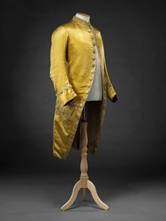 Coat, 1770s. Yellow silk satin, edges and pocket flaps embroidered with small floral motifs in cream and black silk, fabric-covered and embroiderd buttons, silk lining.