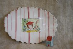lady in red hat in her garden, with pink / raspeberry stripes on porcelain plate,  by julie whitmore