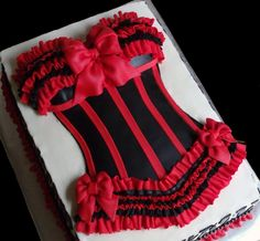 Sexy red and black bustier cake made for a bridal shower where lingerie was the focus of the party! Chocolate cake, half with raspberry filling, half with vanilla filling; bustier was made of cake as well, then frosted, covered and decorated with fondant. Accented with zebra stripes and red ruffles to go with the shower decorations.
