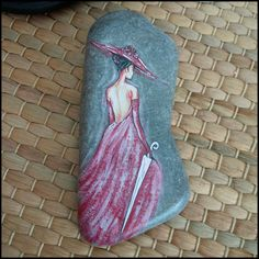 Woman in Red - hand made, acrylic painted stone. Stone approx. 15cm. long. She made broken look beautiful and strong look invincible. She walked with the Universe on her shoulders and made it look like a pair of wings. ― Ariana Dancu This stone is talking about a strong and beautiful woman. Her beauty is not a red dress, her beauty is her naked soul.