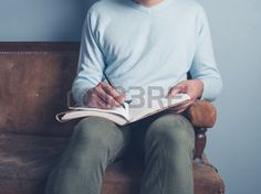 university students: A young man is sitting on an old sofa and is writing in a notebook