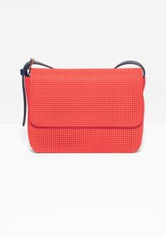 CLARE VIVIER Perforated leather in electric red adds a sporty vibe to this compact leather shoulder bag with a contrasting adjustable shoulder strap for multiple styling options.