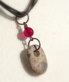 Pebble jewelry. Beach stone necklace and garnet bead from Spain by oceangifts. Drilled beach pebble jewelry.