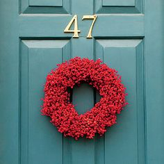 Use Bold Color | A bold shade of red instantly brings Christmas cheer to any front door. This simply stated version adds the perfect festive touch.