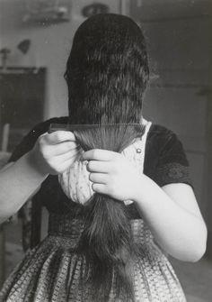 Demonstratie van het 'kapzetten' van de 'lange muts' te Westkapelle. 1956 De grootste hoeveelheid haar wordt naar voren gekamd. De rest van het haar wordt naar achteren gekamd. Dit kammen wordt door het meisje zelf gedaan. Meestal wordt vervolgens de muts door haar moeder gezet. #Zeeland #Walcheren
