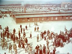 Here a view of the Buchenwald Concentration Camp at Weimar Germany, taken from the tower over the main entrance gate. Only about one-third of the barracks building can be seen. Prisoners able to leave waiting for transportation to Displaced Persons Camps, where they will be processed prior to repatriation. American soldiers in he picture are making a tour of the camp