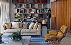 A ideia era fazer um home office na sala de um jovem recém-casado. A solução do arquiteto Diego Revollo foi projetar uma estante de pau-ferro natural. Na parte de baixo, um painel ripado esconde documentos, pastas e impressora
