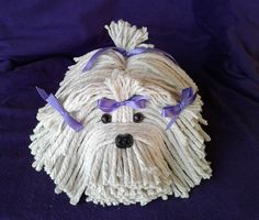 Adorable puppy dog made from a mop head. Cute dog nose and realistic brown eyes. Has purple satin ribbons tied on the head, ears, and tail. Makes a great gift for someone you love. Give the dog as a gift to a special pet owner, custodian, significant other, or collector. This is a