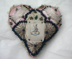 """Antique Antique Pincushion, has regimental insignia for the IX The Norfolk Regiment and the messages """"Forget Me Not"""" and """"Best Wishes."""" Decorated with blue & green beads, trimmed with pink & cream fringed braid, embroidered rays of metallic covered thread, 7.5"""" wide, 7"""" across, 2.5"""" deep, typically such pincushions given by soldiers to sweethearts & wives as memento, rather than for practical use."""