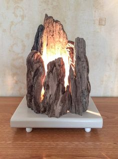"Lamp composed of different pieces of sharp-edged driftwood in the form of ""rocks"" on a wooden base painted beige color resting on four small white wooden f"
