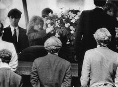 David's sister Courtney placing flowers on David's coffin prior to his burial. Brother Max to her right.