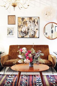#Eclectic living room with mid-century pieces, a beautiful #floral arrangement and #tribal #rug