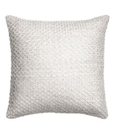 White/silver-colored. Cushion cover in a soft, textured knit with glittery threads and sequins. Concealed zip.