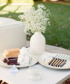mini chocolate bars, marshmallows, and graham crackers set out on plates.