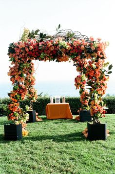 Orange and coral wedding ceremony alter decor / http://www.deerpearlflowers.com/36-fall-wedding-arch-ideas-for-rustic-wedding/