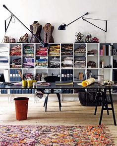 large floating desk, swing arm lamps, wall of cube shelving units