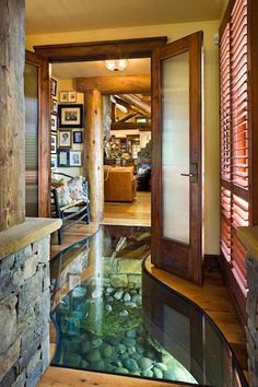 The foyer in this house is built from reclaimed wood over a creek in Wyoming, a concept developed by artist Debbie Petersen and her late husband. The home's geo-thermal cooling system uses a pump to channel ground water through conduits under the house, which doesn't just save energy - it also creates the innovative glass-covered indoor stream. Beautiful!