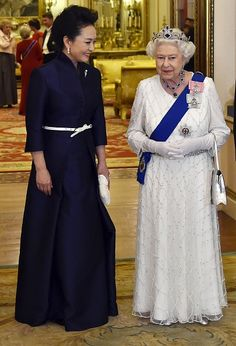 Peng Liyuan (L), the wife of President of China Xi Jinping, accompanies Britain's Queen Elizabeth II (R) as they arrive for a state banquet at Buckingham Palace on October 20, 2015 in London, England.