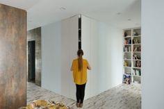 Apartment Hidden Storage White Sleek Wall Panel Large Modern Floor To Ceiling Bookshelf Metal Coated Industrial Wall Scruffy Looking Floor Industrial And Scruffy Stylish Bachelor's Apartment