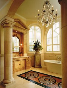 Luxury bathroom with @BainUltra air jet bath tub - A Master Bath remodel inspired by a trip to Italy. Tall ceilings and windows allowed for a 14' architectural vanity, complete with pediment and fluted pilaster side cabinets. The inset marble mosaic forms a carpet between the his and hers vanities and the #BainUltra air jet bath #tub. The oversize crystal chandelier anchors the large space. Photography by George Lambros