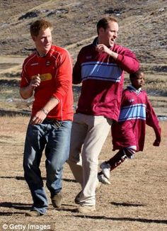 Prince Harry and Prince William play in a football match during a visit to a child education centre on June 2010 in Semonkong, Lesotho.