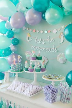 Mermaid themed children's birthday party dessert table. Cake, cupcakes, cookies, and candy. Decorated with turquoise and purple balloons and tassels. Mermaid Party styling by Happy Wish Company. Photography by Tammy Hughes Photography. Stationery by Minted artist, Bonjour Paper.