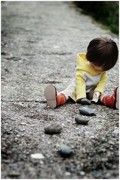 So cute and....contrasting. The little child on hard, gray rock. Bright and carefree against realistic and normal.
