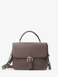 Preppy meets polished with the Cooper satchel. The luxe pebbled leather exterior features a single top handle and adjustable shoulder strap, while refined hardware and a buckled flap fastening round out this timeless, tailored design.