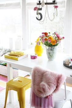 What a colourful little area, love it! The colours are bright, but very harmonious which creates a happy feeling of well being. Love how the unique and clean black chandelier grounds the energy of the space without being too heavy.  Excellent for a South (fire element feng shui) area living room.