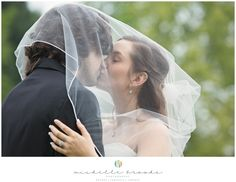 Bride and groom share a kiss under the bridal veil. Chelsea + Daniel's wedding at Lenora's Legacy Estate. Image credit: Michelle Brooks.