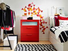 Uma cómoda com 3 gavetas em vermelho, encostada a uma parede branca com um padrão geométrico em amarelo, vermelho, laranja e rosa