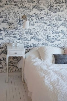 Blue toile wallpaper in an otherwise white room