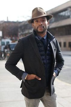 Men's Brown Hat, Charcoal Longsleeve Shirt, Navy Tie, Grey Jeans, Charcoal Wool Blazer, and Navy Quilted Gilet