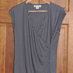 Great work top!  Black and white faux wrap. Great top for work with pants and skirts. Faux wrap look on front with slight pleating.  Never worn Liz Claiborne Tops Blouses