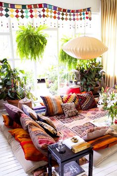 Rook with patterned rug and patterned pillows, white light fixture, large glass windows, white floors, black coffee table, flowers and plants