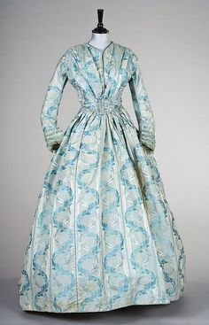 A rare blue silk damask maternity gown, late 1840s-early 1850s, the bodice with two openings over the breasts concealed within the fan-pleating with hook and eye fasteners to the inner cotton lining, full, round skirt, the fabric woven with lily of the valley and foliate lattice,
