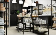 A boutique with black shelving units and a wash-stand with drawers