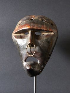 Katoyo mask from the Chokwe, Angola. The Katotyo represents the foreigner: thin nose, pronounced chin, and the eyes hidden under the colonial mask.
