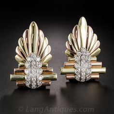 A striking amalgam of 1930s Art Deco and 1940s Retro styles coalesce in this spectacular brooch and double clips combo, artistically (and substantially) rendered in contrasting 15K pink and green gold (thus most likely of British origin) and overlaid with platinum and diamonds. The geometric center sections are reminiscent of a pan flute or organ pipes and flare out in both directions in a dramatically stylized wing motif.