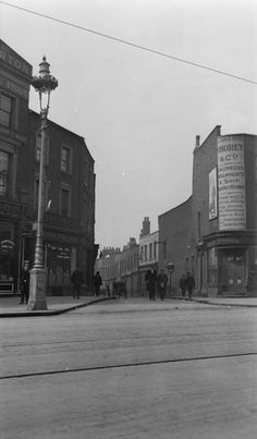 General view of the entrance to the Limehouse Causeway at West India Dock showing a variety of shops at the entrance.(Linney, A.G. 1926-1935)