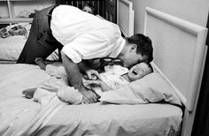 Robert Kennedy putting one of his sons to bed