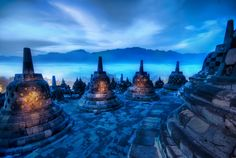 "'The Beating Hearts of the Buddhas,' Jakarta, Indonesia | Trey Ratcliff (Stuck in Customs), on Flickr. Each bell case holds a solitary outward-facing Buddha. Photographer wrote: ""The morning fog coming off the top of the jungle trees was not like anything I had seen before. There was just enough morning light to give everything a twilight blue and paint the mountains in the distance a deeper color."" <-- This is such a cool photo! #blue #color #buddha #bell #cages #sunrise #sunset #fog…"