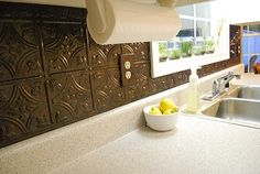 Faux-tin tile backsplash.  Nice, I like that you can cover the face plates of outlets as well