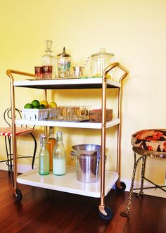 bar cart. antique rescued from a yard sale, spray painted, and outfitted with turkish tea glasses and glass carafes.