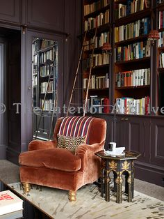 Deep cupboards surround the door to the study and the bookshelves are accessed by a sliding bronze ladder