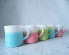 "Five iconic 1950s Hazel Atlas coffee mugs in turquoise, pink, and green fade, better known as ""Crinoline or Ripple."""