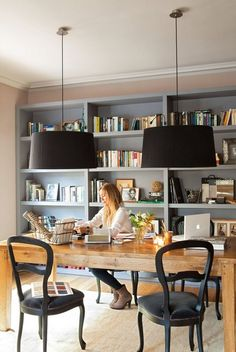home office space; gray bookshelves, black pendant lamps.