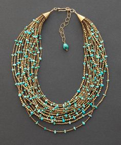 Turquoise multi strand necklace created with 17 strands of tribal brass beads from India and genuine turquoise nugget beads from both the Kingman and No. 8 mines. One of a kind ethnic jewelry by Angela Lovett Designs