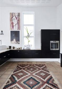 Modern and black wall-mounted kitchen from HTH. The ethnic carpet provides a cozy atmosphere.